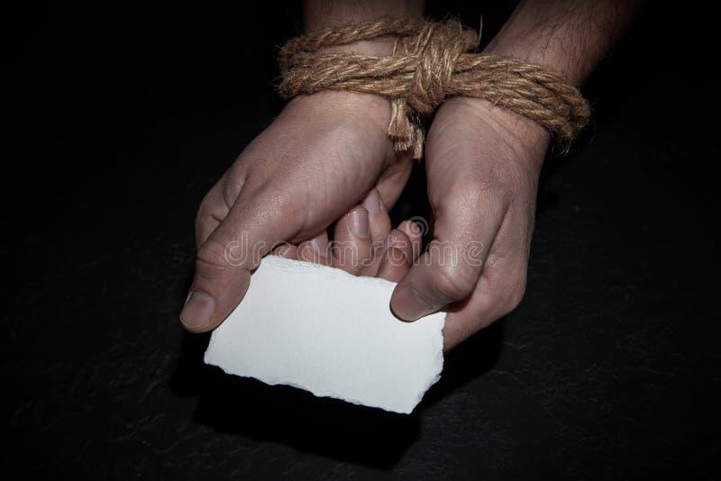 El hombre con sus manos atadas con una cuerda está llevando a cabo un trozo de papel vacío Concepto de la esclavitud, por favor a foto de archivo