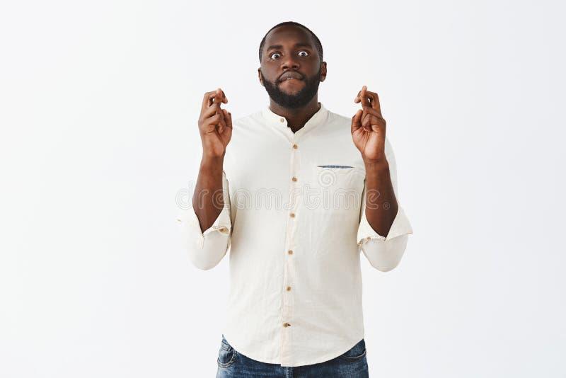 El hombre con todo los fingeres que cruzan y de la esperanza y labio penetrante mientras que nervioso espera resultados important foto de archivo