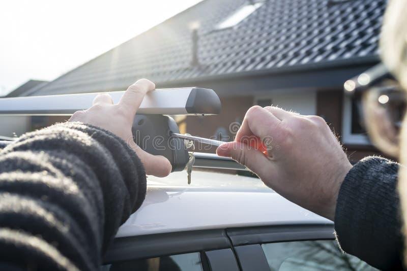 El hombre con un destornillador instala los accesorios para la caja del tronco o del cargo en el tejado del coche, en los rayos d foto de archivo libre de regalías
