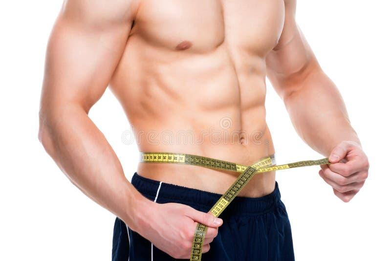 El hombre con un torso muscular utiliza a la cinta métrica foto de archivo libre de regalías