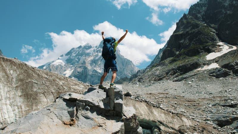El hombre con un turista de la mochila sube en una roca y aumenta sus manos para arriba en las montañas de las montañas en la cam fotografía de archivo libre de regalías