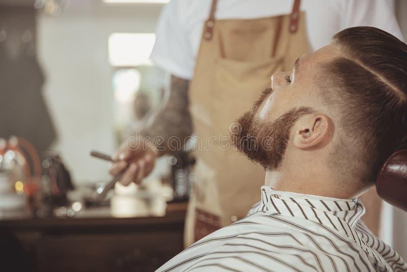 El hombre con una barba espera un afeitado con una maquinilla de afeitar en una barbería imágenes de archivo libres de regalías