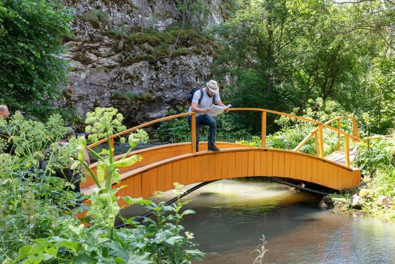 El hombre con una barba está estudiando el mapa al aire libre concepto de turismo ecológico, viaje independiente los fotógrafos t imagen de archivo