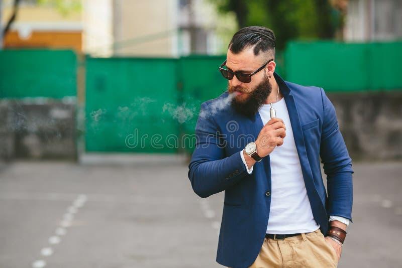 El hombre con una barba fuma el cigarrillo electrónico imagenes de archivo