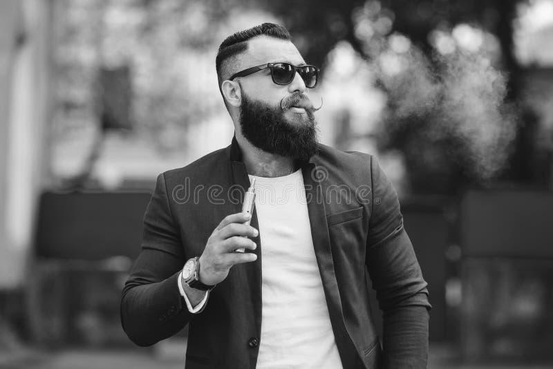 El hombre con una barba fuma el cigarrillo electrónico foto de archivo libre de regalías