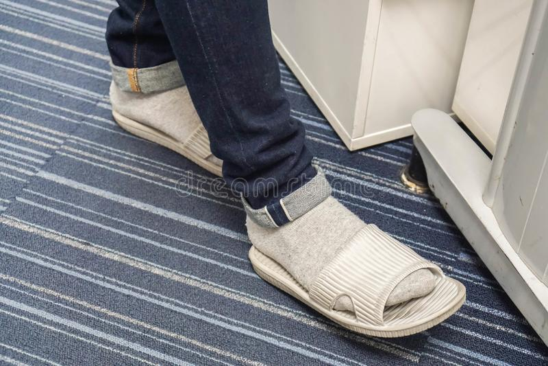 El hombre con vaqueros azul marino lleva los deslizadores grises con los calcetines en oficina imagenes de archivo