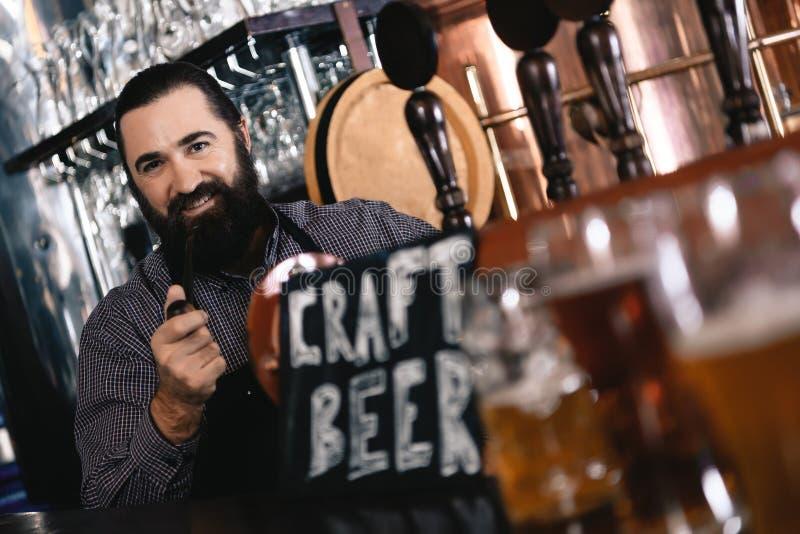 El hombre confiado barbudo fuma el tubo en el contador de la barra de la cervecería brewing Cervecería El hacer a mano de la cerv imagenes de archivo