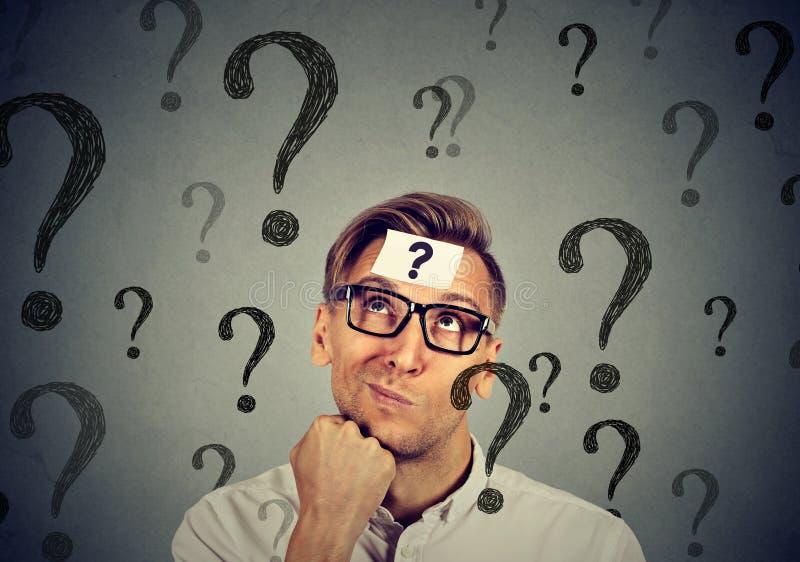 El hombre confuso pensativo tiene muchas preguntas ninguna respuesta foto de archivo