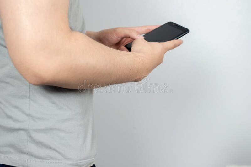 El hombre consume su teléfono móvil, cierre imagen de archivo