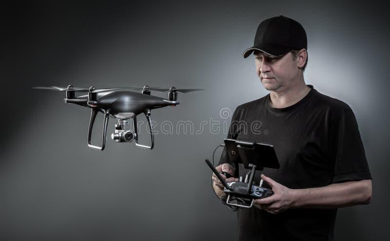 El hombre controla un quadrocopter El foco selectivo en hombres, abej?n se empa?a imagenes de archivo