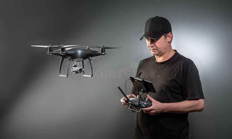 El hombre controla un quadrocopter El foco selectivo en hombres, abej?n se empa?a fotos de archivo libres de regalías