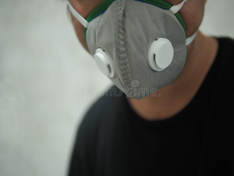 El hombre corporativo que lleva una máscara protectora para la contaminación atmosférica, protege contra la contaminación por la  imagen de archivo libre de regalías