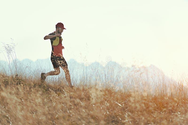 El hombre corre cuesta abajo entre los prados de la montaña del otoño imágenes de archivo libres de regalías