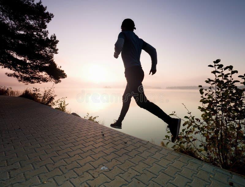 El hombre corre en el pavimento en bah?a del lago Entrenamiento regular de la ma?ana fotos de archivo