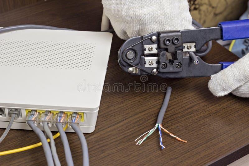 El hombre corta el cable de la red, el módem en la tabla, el router, el cable de la red, un módem del primer foto de archivo libre de regalías