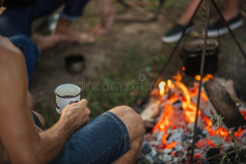 El hombre cosechado de la foto se está sentando con té cerca de la hoguera fotos de archivo