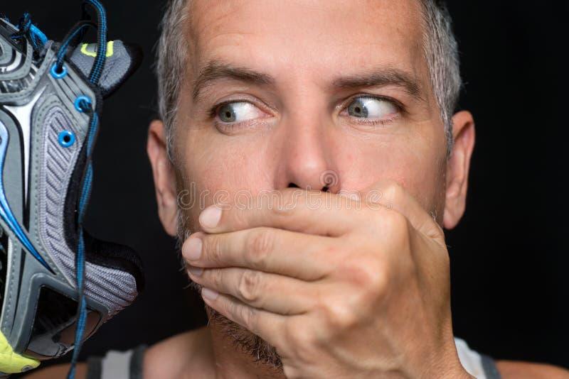 El hombre cubre la boca después de oler el zapato foto de archivo libre de regalías