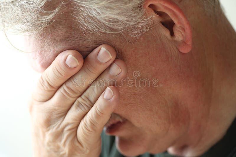 El hombre cubre la cara con la mano imagen de archivo libre de regalías