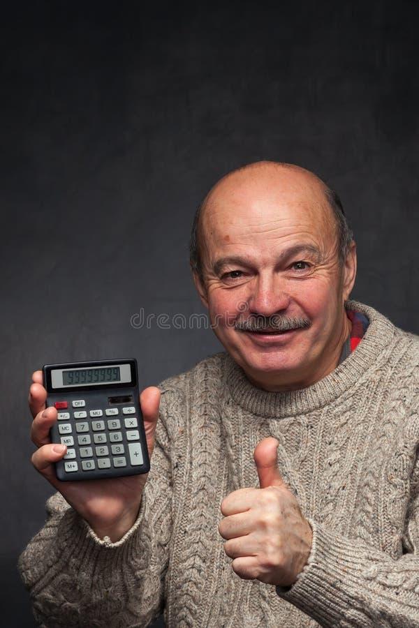 El hombre cuenta los ingresos y el beneficio y muestra los pulgares para arriba imágenes de archivo libres de regalías