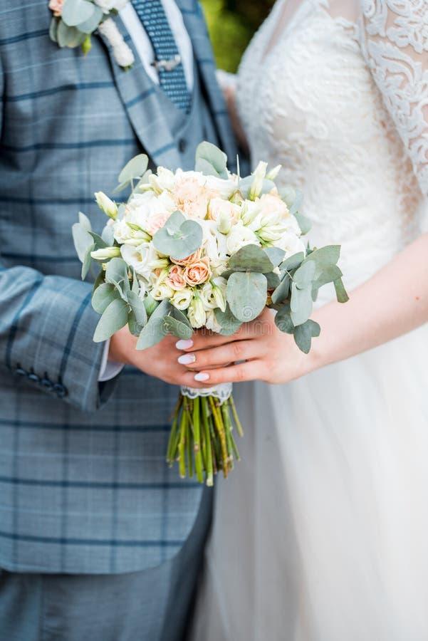 El hombre da a la muchacha de flores de la boda Primer Ramo de la boda El ramo nupcial hermoso en manos de la novia joven se vist fotos de archivo libres de regalías