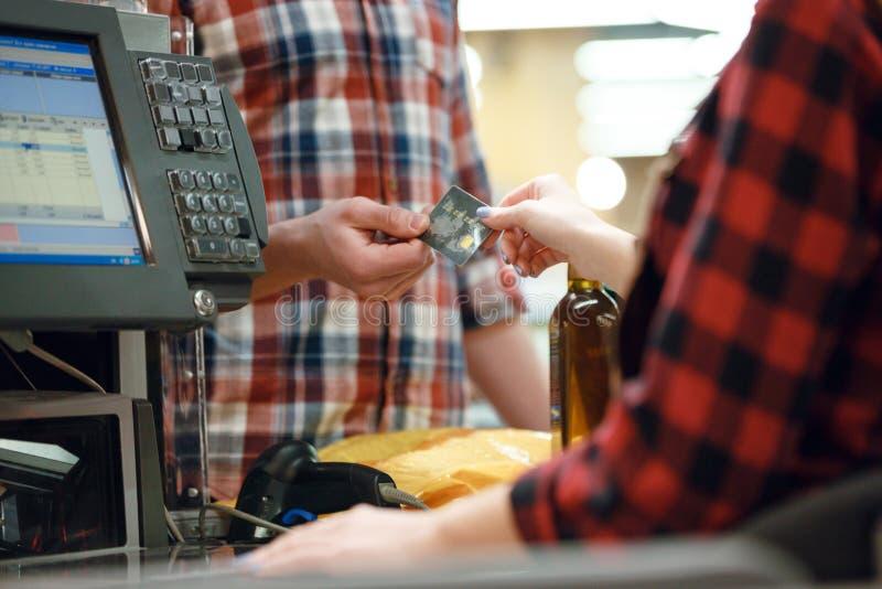 El hombre da la tarjeta de crédito a la señora del cajero en supermercado fotos de archivo