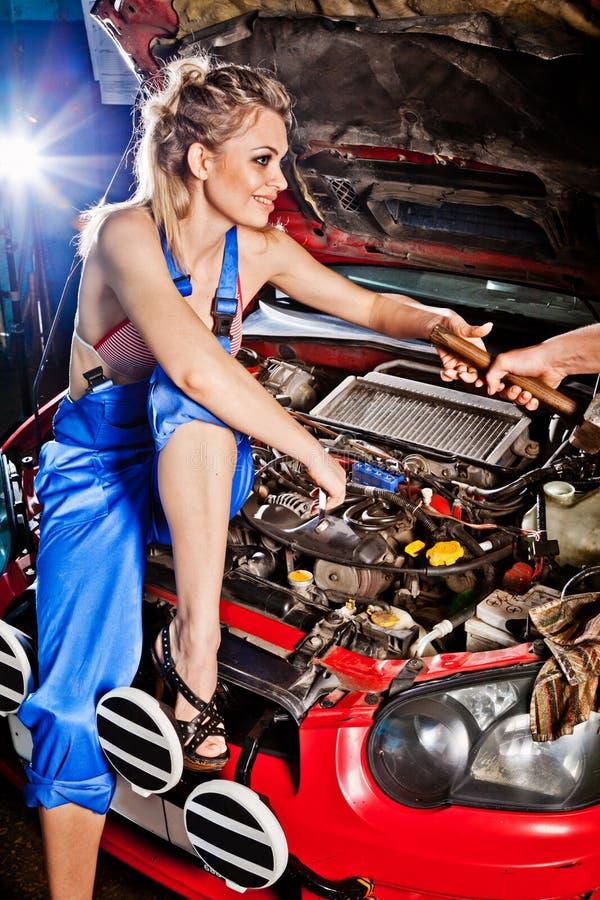 El hombre da a muchacha una herramienta para reparar un coche foto de archivo libre de regalías