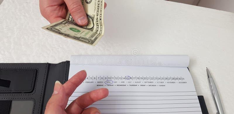 El hombre da un billete de dólar a una mano de la mujer fotos de archivo