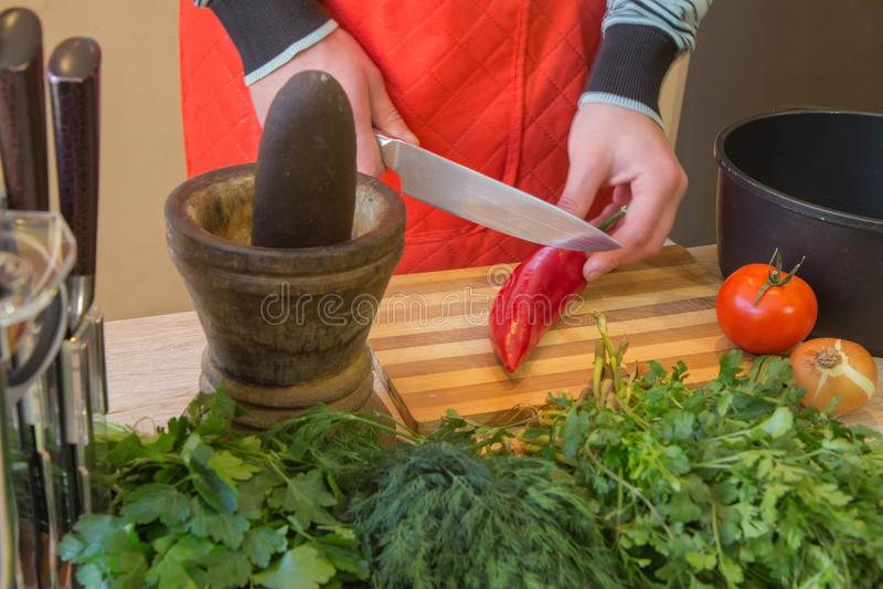 El hombre da verduras del corte en la pizarra de la cocina Alimento sano Varón que prepara verduras imagen de archivo