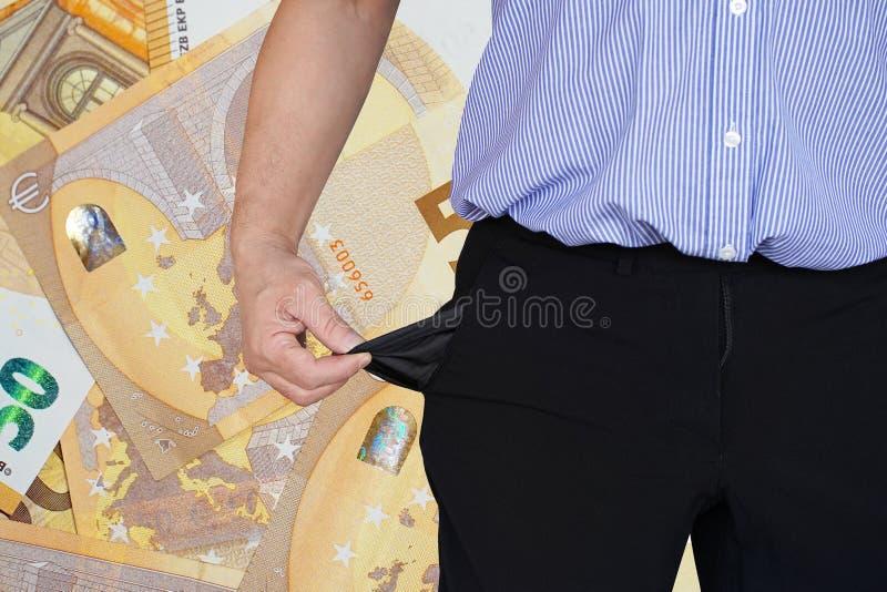 El hombre da vuelta encima de su bolsillo del pantalón Fondo del euro 50 en el fondo imagen de archivo libre de regalías