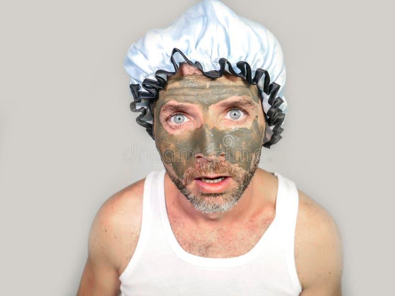 El hombre de aspecto extraño con el casquillo y la crema de ducha en su cara horrorizó verse feo en el espejo del cuarto de baño  foto de archivo libre de regalías