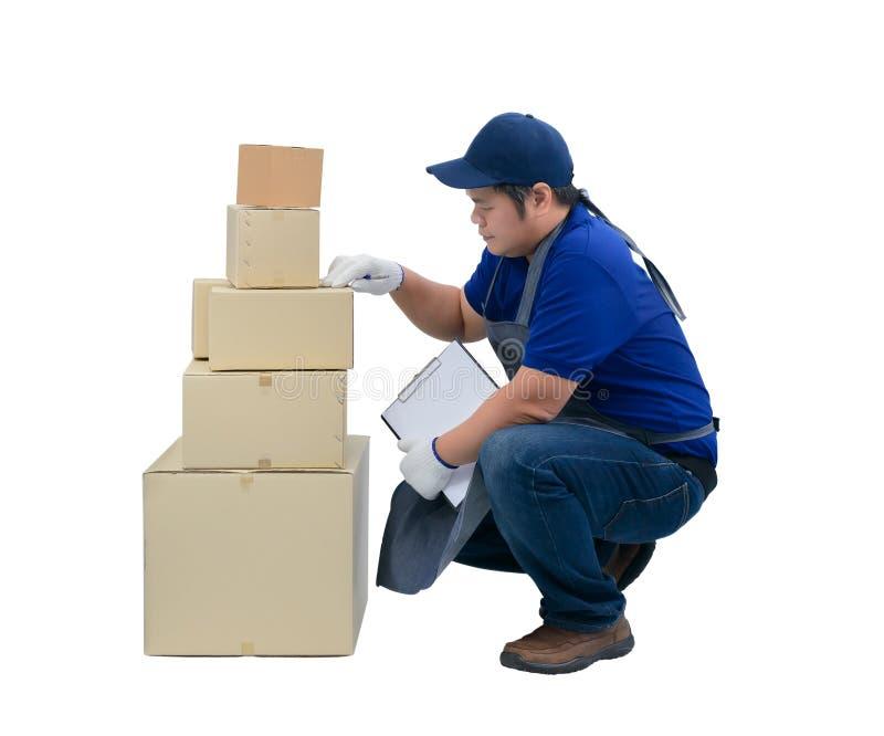 El hombre de entrega asiático que trabaja en delantal azul de la camisa, los guantes protectores es de comprobación o de cuenta d imagen de archivo libre de regalías