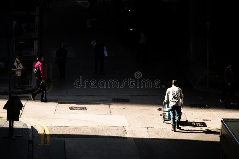 El hombre de entrega empuja un carro a través de un pequeño empalme en el callejón trasero de Hong Kong imágenes de archivo libres de regalías