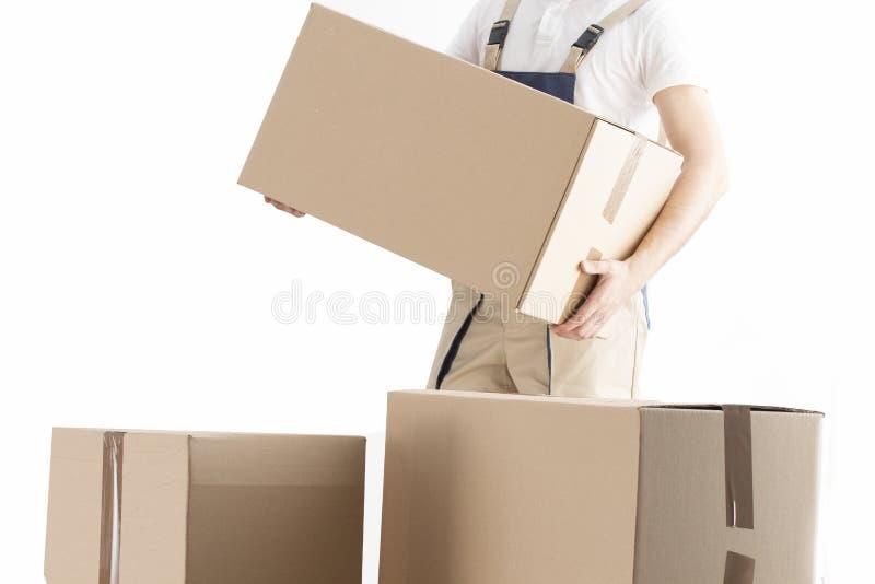 El hombre de entrega pone la caja de cartón Concepto del servicio de la relocalización Cargador con la caja Motor en uniforme imagen de archivo