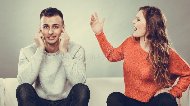 El hombre de griterío de la mujer enojada de la furia se cierra los oídos fotografía de archivo libre de regalías