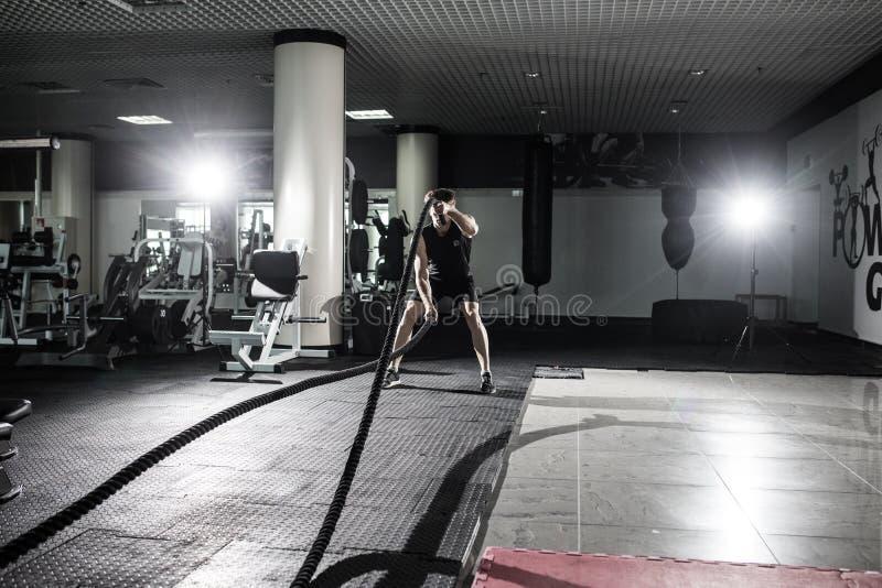 El hombre de la aptitud que se resuelve con batalla ropes en el gimnasio Luche al hombre de la aptitud de las cuerdas en el cuerp imagenes de archivo