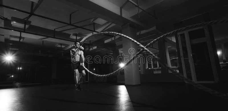 El hombre de la aptitud que se resuelve con batalla ropes en un gimnasio imagen de archivo libre de regalías