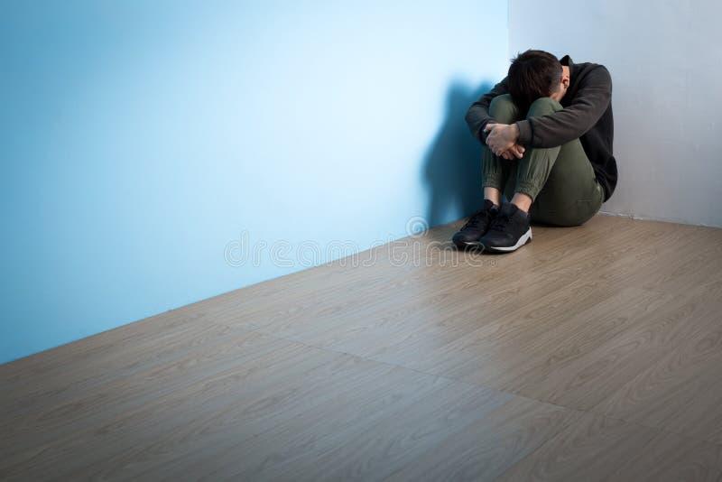 El hombre de la depresión se sienta en piso imagenes de archivo