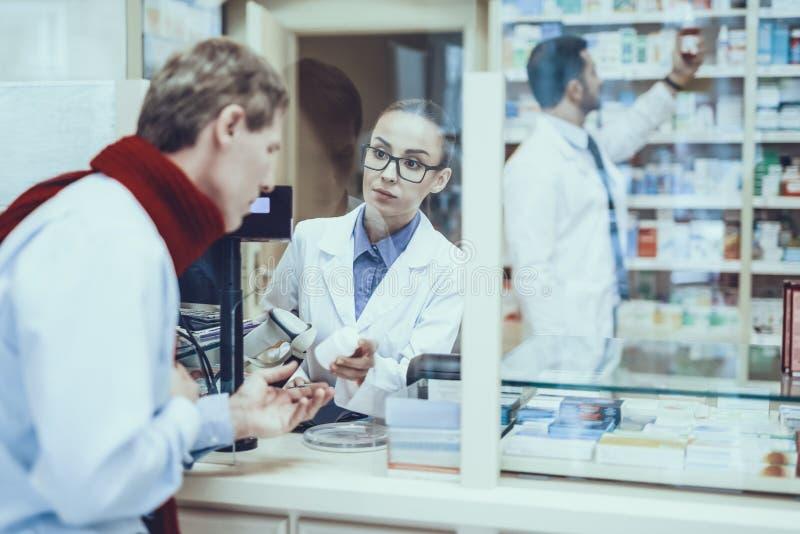 El hombre de la enfermedad compra un medicamento en farmacia imagen de archivo