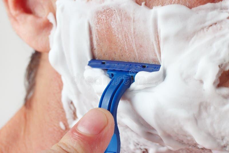 El hombre de la mano afeita su primer de la mejilla imagen de archivo