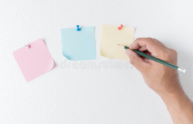 El hombre de la mano escribe en la nota de papel con el perno en la hoja de la espuma fotografía de archivo libre de regalías