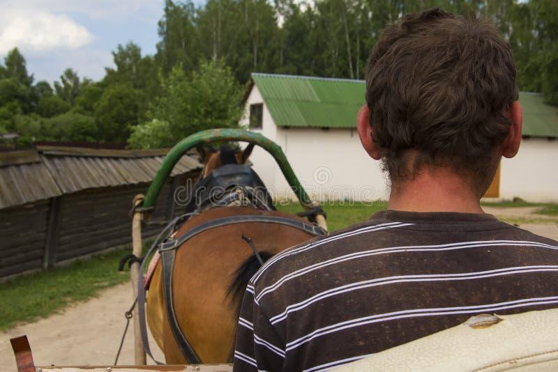 El hombre de la opinión del fondo funciona con un carro rural con un caballo, un museo de la vida rural fotos de archivo libres de regalías