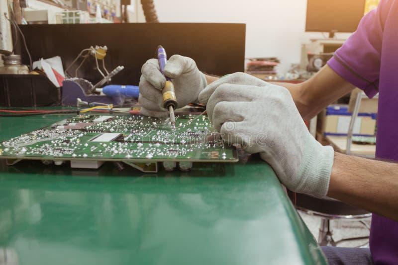 El hombre de la reparación que usa la medida del multímetro digital en el circuito del tablero del PWB imágenes de archivo libres de regalías
