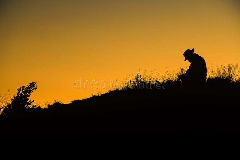 El hombre de la silueta separó la mano encima de una montaña que disfrutaba de puesta del sol fotos de archivo