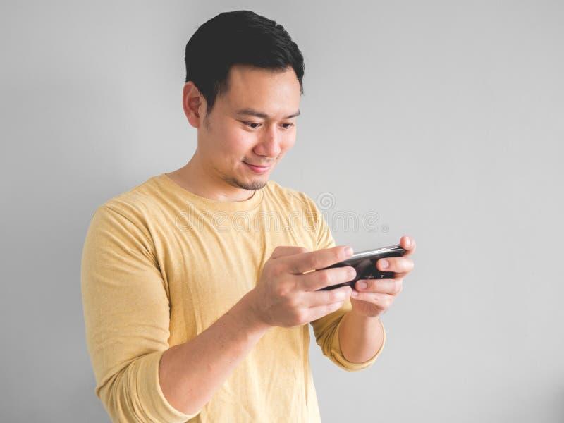 El hombre de la sonrisa juega al juego móvil imagen de archivo