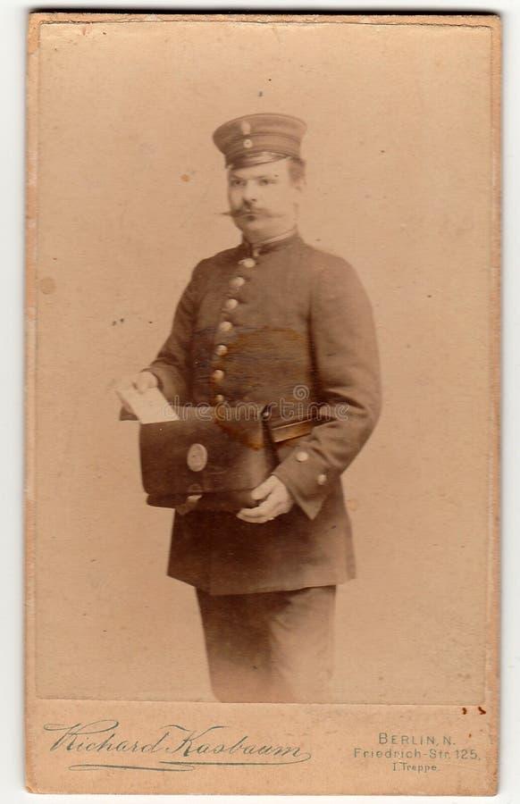 El hombre de las demostraciones de la tarjeta del gabinete del vintage lleva un uniforme del cartero Foto blanca negra antigua fotografía de archivo