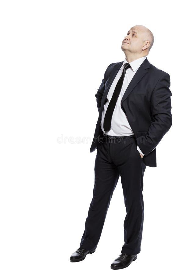 El hombre de mediana edad calvo en un traje en crecimiento completo mira para arriba vertical Aislado en un fondo blanco foto de archivo