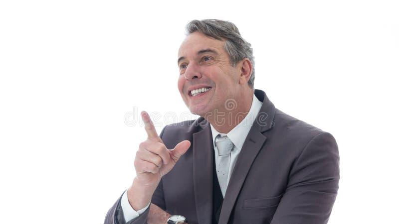 El hombre de mediana edad es feliz y señala hacia arriba Ejecutivo en el traje o fotos de archivo libres de regalías