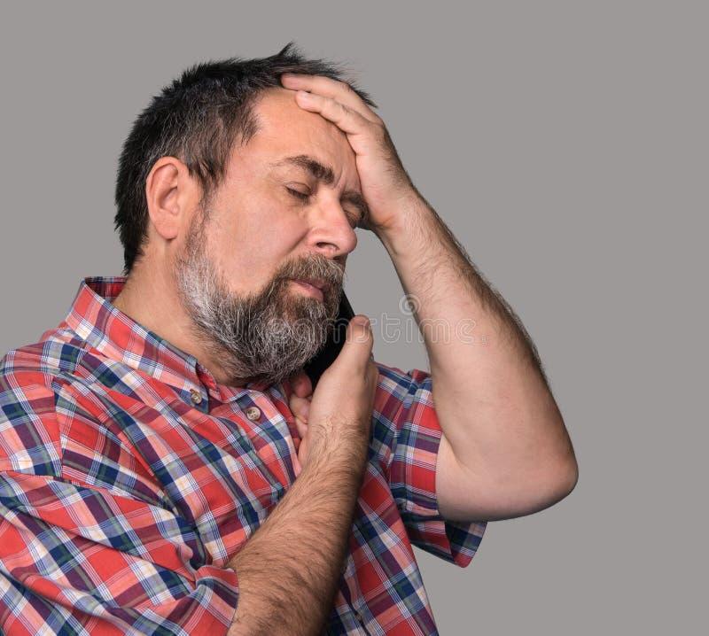 El hombre de mediana edad habla en un teléfono móvil imagen de archivo libre de regalías
