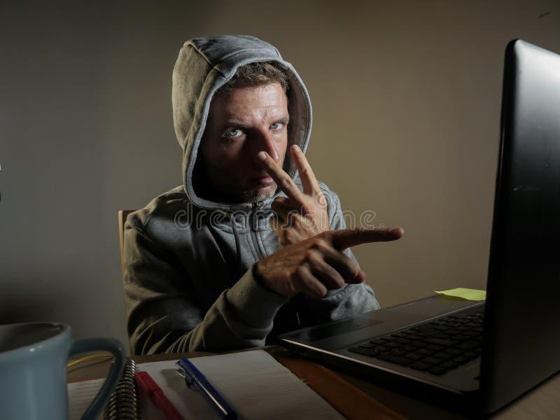 El hombre de mirada peligroso del pirata informático en la sudadera con capucha que corta el sistema informático de Internet que  foto de archivo