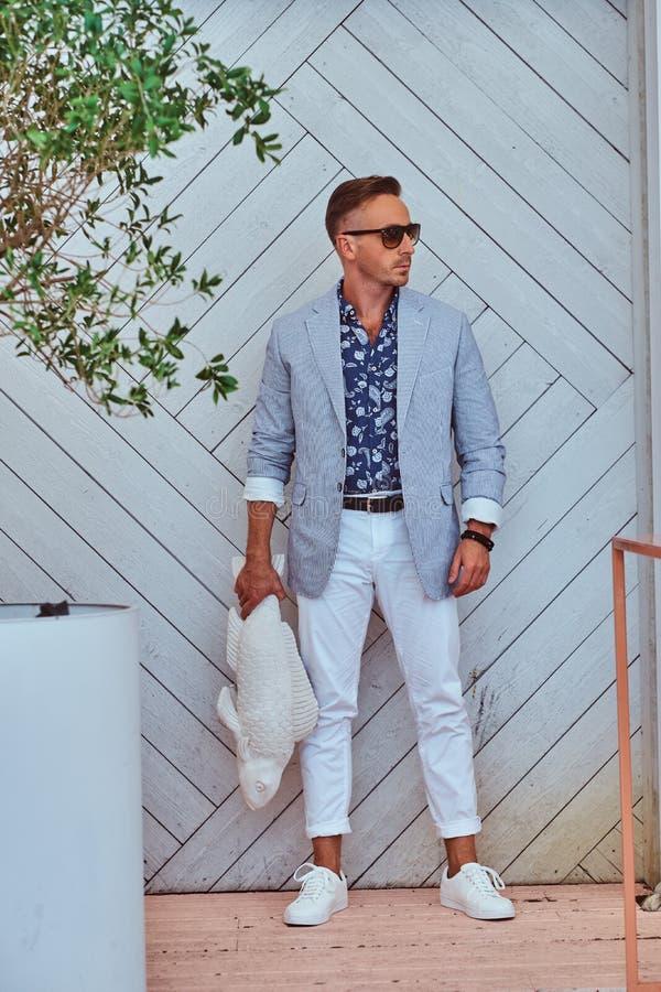 El hombre de moda en gafas de sol vistió en controles elegantes modernos de la ropa una escultura de los pescados mientras que se imágenes de archivo libres de regalías